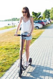 Beztroska kobieta jedzie na skuterze