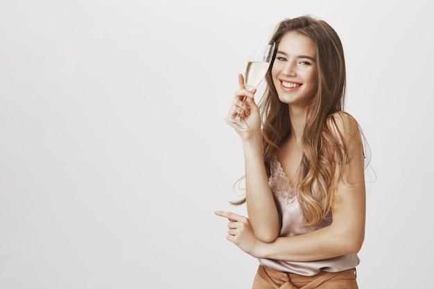 Beztroska kobieta pije szampana i śmieje się z imprezy