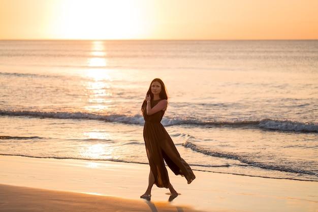 Beztroska kobieta podziwiając zachód słońca na plaży. szczęśliwy styl życia