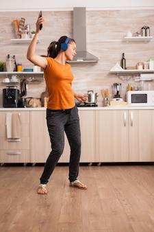 Beztroska kobieta tańcząca w kuchni słuchająca muzyki na słuchawkach