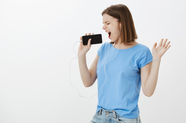 Beztroska kobieta tańczy, gra w aplikację karaoke na smartfonie, śpiewa do telefonu komórkowego i nosi słuchawki