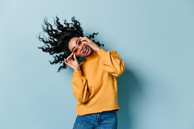 Beztroska kobieta tańczy na niebieskiej ścianie w okularach przeciwsłonecznych