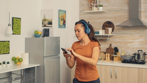 Beztroska kobieta tańczy w kuchni słuchając muzyki na słuchawkach. energiczna, pozytywna, szczęśliwa, zabawna i urocza gospodyni tańcząca samotnie w domu. rozrywka i wypoczynek samemu w domu