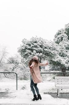 Beztroska Kobieta W Ciepłych Ubraniach, Obracająca Się Z Rozpostartymi Ramionami, Ciesząc Się śnieżnym Dniem Zimą W Parku Premium Zdjęcia