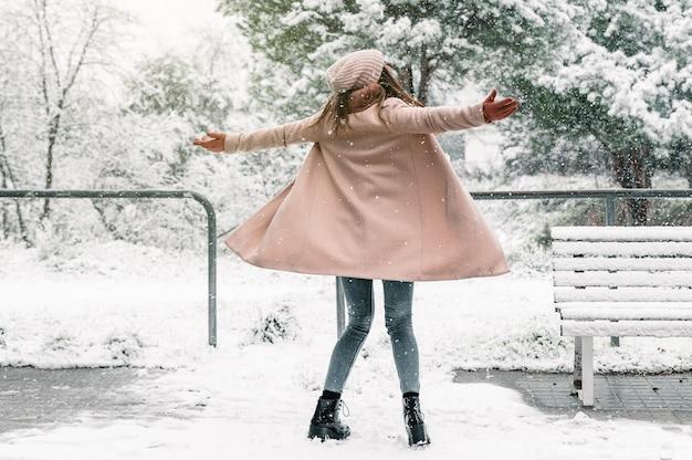 Beztroska kobieta w ciepłych ubraniach, obracająca się z rozpostartymi ramionami, ciesząc się śnieżnym dniem zimą w parku