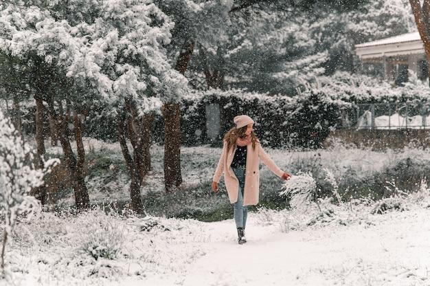 Beztroska kobieta w ciepłym płaszczu i kapeluszu spaceruje ścieżką w lesie, podziwiając przyrodę zimą