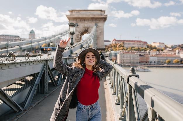 Beztroska kobieta w dorywczo czerwony sweter ciesząc się życiem i pozując na tle miasta