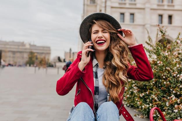 Beztroska kobieta w eleganckich włosach siedzi na ziemi i rozmawia przez telefon