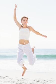 Beztroska kobieta w skakaniu na plaży