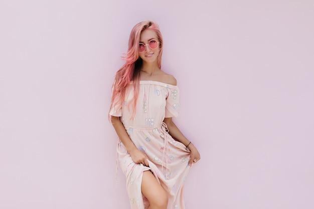 Beztroska kobieta w stylowej letniej sukience pozuje z uśmiechem zainteresowania.