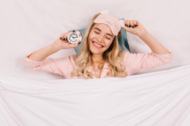 Beztroska kobieta z zegarem leżącym na poduszce