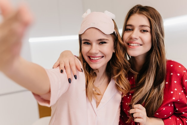 Beztroska kręcona dziewczyna w różowej masce na oczach robi selfie z najlepszym przyjacielem. kryty zdjęcie romantycznej ciemnowłosej pani ze szczerym uśmiechem, która rano bawi się.
