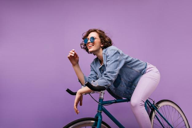 Beztroska krótkowłosa pani siedzi na rowerze. szczęśliwa dziewczynka kaukaski wyrażająca pozytywne emocje z falistą fryzurą.