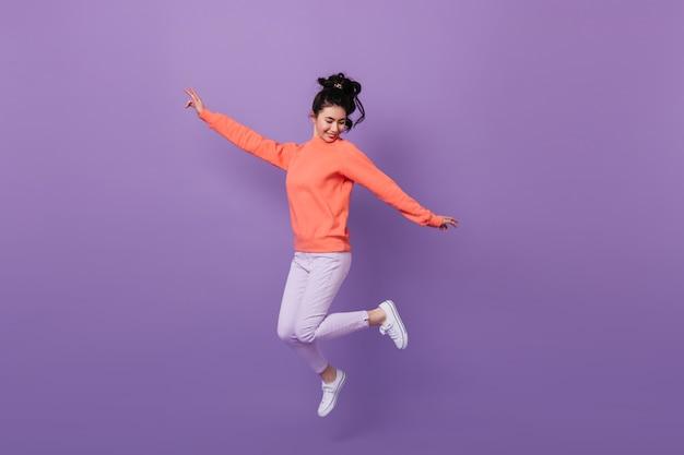 Beztroska ładna azjatykcia kobieta skacze z uśmiechem. strzał studio śmieszne kobiety koreański taniec na fioletowym tle.
