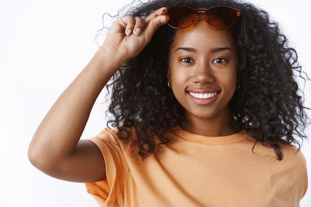 Beztroska, ładna studentka spędzająca weekendy imprezująca z przyjaciółmi przy basenie stojąca zadowolona, szczęśliwa uśmiechnięta biała ściana, zdejmująca okulary przeciwsłoneczne, rozmawiająca z chłopakiem, uśmiechnięta usatysfakcjonowana