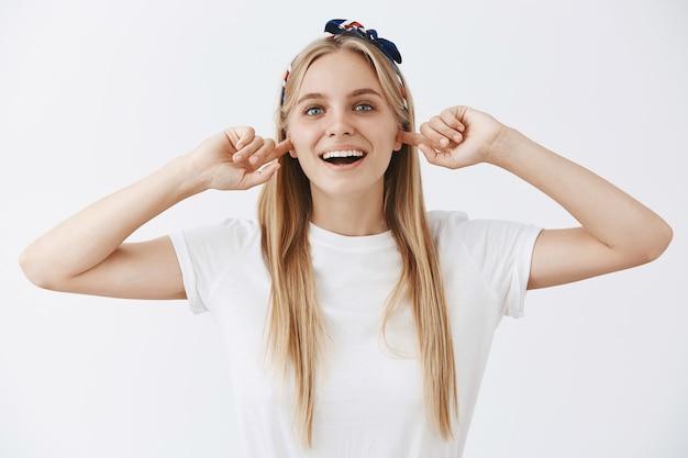 Beztroska młoda blond dziewczyna pozuje na białej ścianie