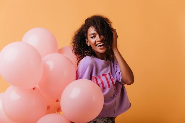 Beztroska młoda dama trzyma balony z helem na pomarańczowo i uśmiecha się. śmiejąca się pozytywna czarna dziewczyna obchodzi urodziny.