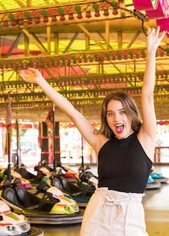 Beztroska młoda kobieta cieszy się przy parkiem rozrywki