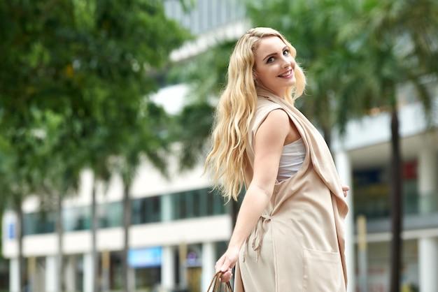 Beztroska młoda kobieta cieszy się spacer w mieście