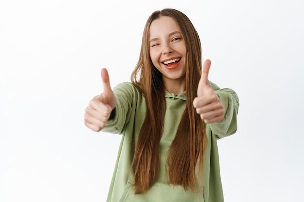 Beztroska młoda kobieta wyciąga kciuki w górę i mruga do ciebie, chwali dobrą robotę, świetną robotę, poleca coś fajnego, polub i mówi tak, stojąc nad białą ścianą