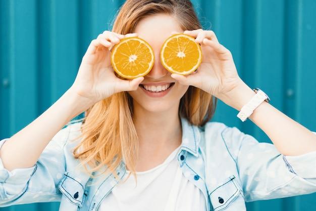 Beztroska młoda piękna dziewczyna używa dwóch połówek pomarańczy zamiast okularów na oczach