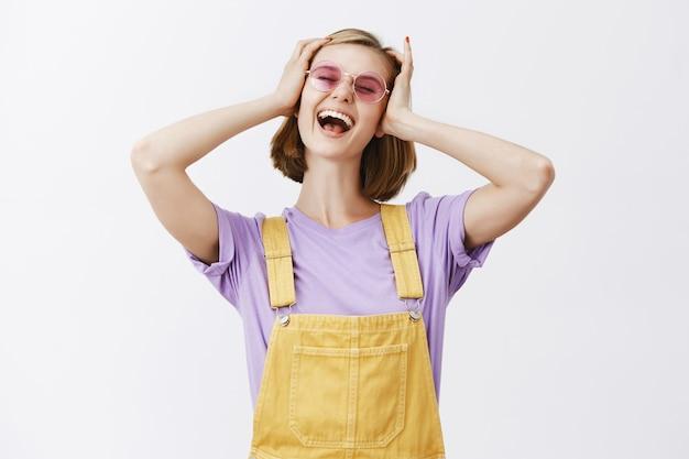 Beztroska młoda stylowa kobieta w okularach przeciwsłonecznych i letnich ubraniach krzyczy podekscytowany