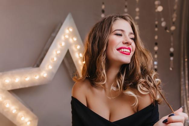 Beztroska modna kobieta bawi się błyszczącymi kręconymi włosami na ciemnej ścianie. zrelaksowana młoda dama z romantyczną fryzurą śmiejąca się podczas wakacyjnej sesji zdjęciowej.