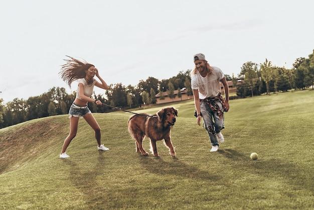 Beztroska niedziela. pełna długość młodej nowoczesnej pary bawiącej się z psem podczas beztroskiego czasu w parku