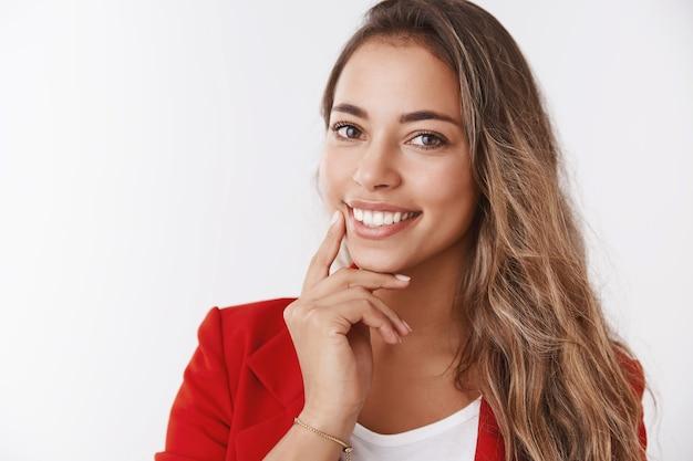 Beztroska, odnosząca sukcesy przedsiębiorczyni wygłaszająca wykład jak stać się pewna siebie bizneswoman uśmiechnięta szeroko pewna siebie dotykając linii szczęki wpatrując się w kamerę pochylając głowę szczerząc zęby białe zachwycone