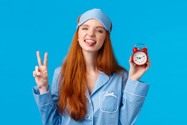 Beztroska, odważna i wesoła młoda rudowłosa nastoletnia zbuntowana dziewczyna nie dba o czas ani zegary, pokazuje czerwony alarm i znak pokoju, mrużąc język, stojąc w piżamie szczęśliwa