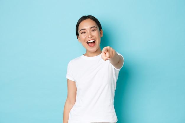 Beztroska, optymistyczna ładna azjatycka dziewczyna w białej koszulce, bawiąca się, śmiejąca się i wskazująca palcem, jakby kpiąca z osoby, bawiąca się zabawnym przyjacielem, stojąca szczęśliwa nad niebieską ścianą