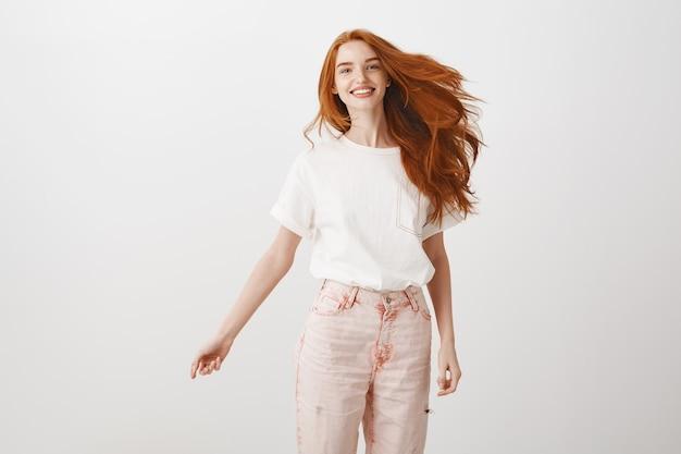 Beztroska, optymistyczna ruda dziewczyna uśmiecha się i skacze ze szczęścia