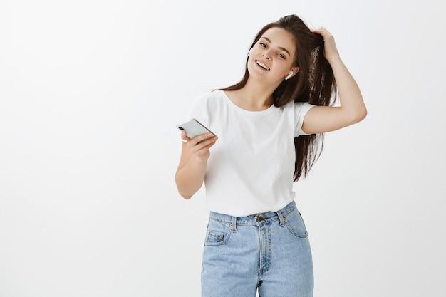 Beztroska pewna siebie młoda kobieta pozuje z telefonem i słuchawkami na białej ścianie