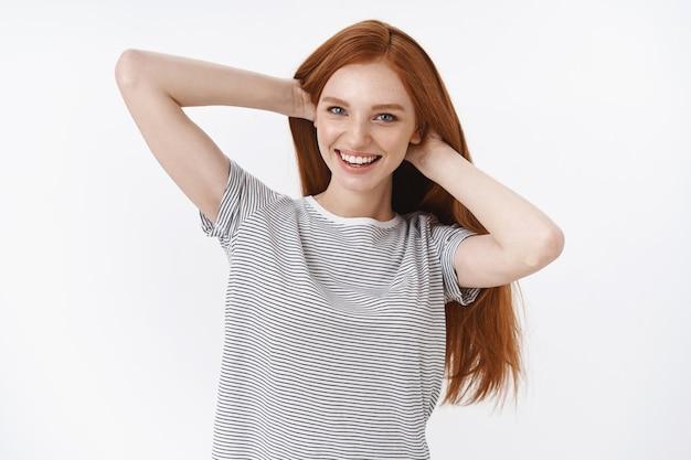 Beztroska pewność siebie elegancka młoda ruda dziewczyna dumna idealna zdrowa ruda długie włosy wzruszająca fryzura uśmiechnięta zachwycona pewna siebie jak świetny szampon polecam produkt do pielęgnacji włosów, biała ściana