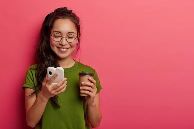 Beztroska piękna dziewczyna czyta zabawny mem w internecie, trzyma telefon komórkowy podłączony do bezprzewodowego internetu, lubi nowoczesną komunikację, świeży napój z papierowego kubka