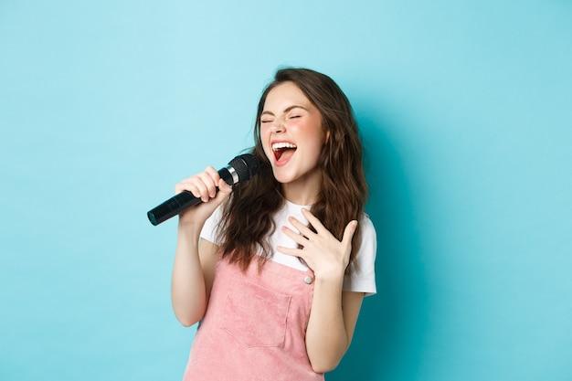 Beztroska piękna dziewczyna wykonuje piosenkę, z pasją śpiewa do mikrofonu, gra karaoke, stoi na niebieskim tle.