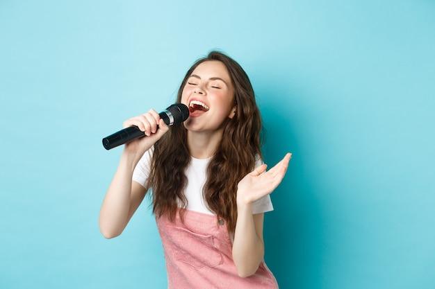 Beztroska piękna kobieta wykonuje piosenkę, z pasją śpiewa do mikrofonu, gra karaoke, stoi na niebieskim tle