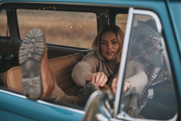 Beztroska podróż. atrakcyjna młoda kobieta dopasowująca but, podczas gdy jej chłopak prowadzi mini vana w stylu retro retro