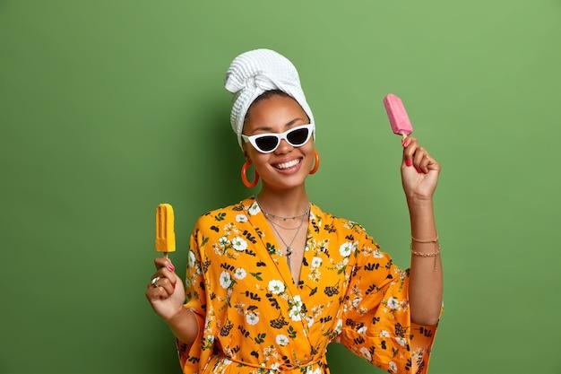 Beztroska, pozytywna ciemnoskóra kobieta trzyma pyszne lody, popsicles na patyku, bawi się latem, nosi stylowe okulary przeciwsłoneczne, żółtą szatę, zawinięty ręcznik na głowie, lubi słodycze.