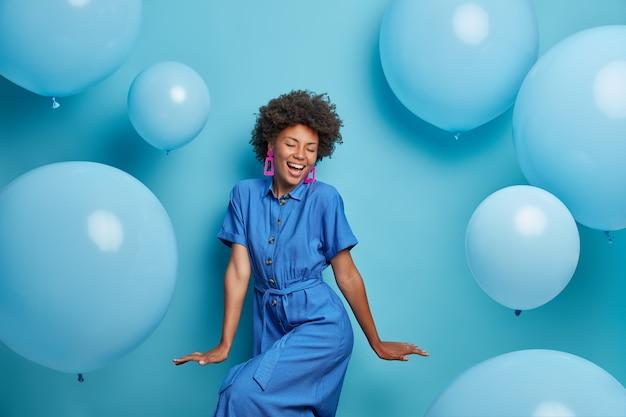 Beztroska radosna, kręcona kobieta radośnie tańczy, ubrana w niebieską sukienkę, ma dreszcze na imprezie wokół nadmuchanych balonów z helem, czuje się wesoła, lubi ulubione wakacje, ma optymistyczny świąteczny nastrój. chwila radości