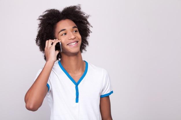 Beztroska rozmowa. wesoły afrykański nastolatek pracujący na cyfrowym tablecie i uśmiechnięty
