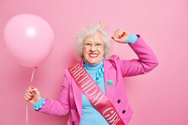Beztroska siwowłosa pomarszczona kobieta tańczy beztroski uśmiech pozytywnie ubrana w odświętne ubrania nosi urodzinową wstążkę trzyma napompowany balon