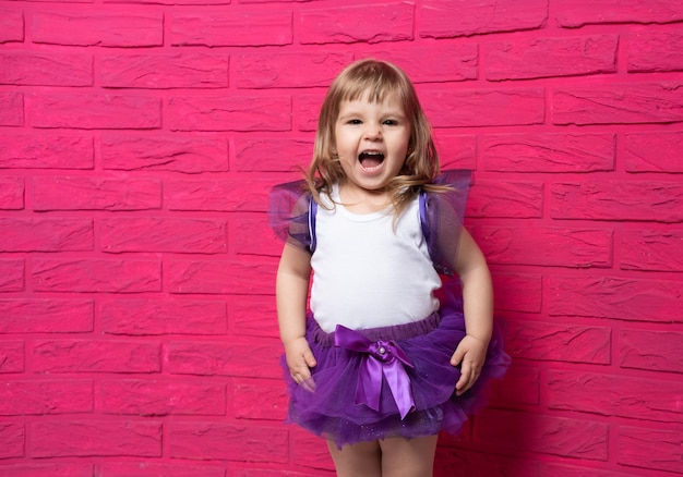 Beztroska śliczna mała dziewczynka w spódnicy tutu śmiejąc się głośno chichocząc na różowej powierzchni.