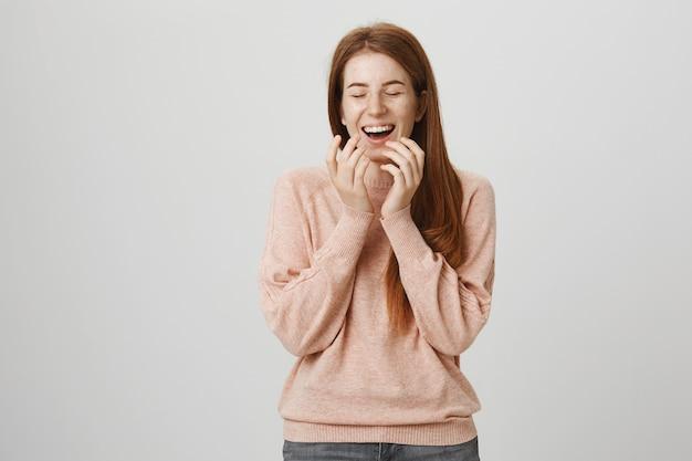 Beztroska śliczna ruda dziewczyna śmiejąca się