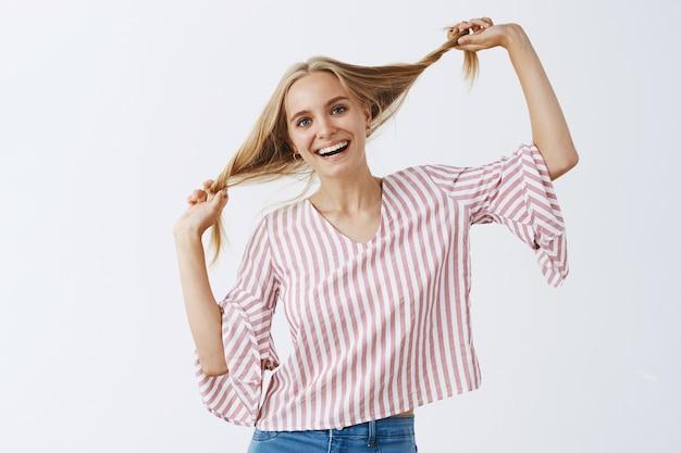 Beztroska stylowa dziewczyna pozuje na białej ścianie