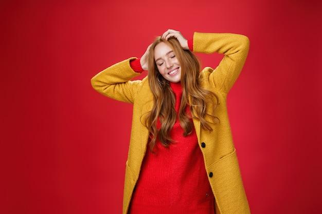 Beztroska szczęśliwa ruda dziewczyna unosząca się z muzyką i dobrymi wibracjami, trzymając ręce na głowie, zamykając oczy i uśmiechając się zachwycona i zrelaksowana bawiąc się, tańcząc na czerwonym tle w żółtym płaszczu.