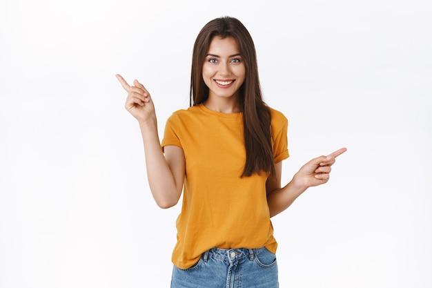 Beztroska, szczęśliwa uśmiechnięta dziewczyna w żółtej koszulce robi zakupy z pewnym siebie, zrelaksowanym wyrazem twarzy, wskazując na boki w lewo i w prawo, dokonując wyboru, prosząc o radę lub sugestie, co lepiej kupić