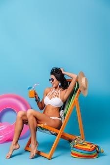 Beztroska szczupła kobieta siedzi na leżaku na niebieskim tle