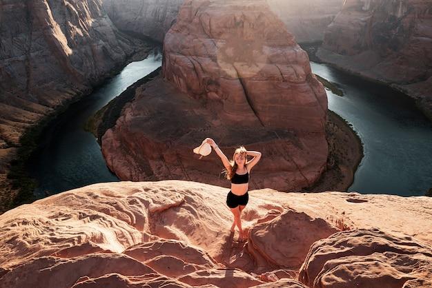 Beztroska turystka na wielkim kanionie młoda kobieta ciesząca się widokiem na zakręcie podkowy w kanionie przygoda ...