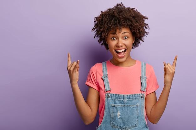 Beztroska, uradowana afroamerykańska dziewczyna krzyczy tak, pokazuje rock and rolla gestem obiema rękami, trzyma usta otwarte, ubrana w stylowe ciuchy, pozuje na fioletowym tle